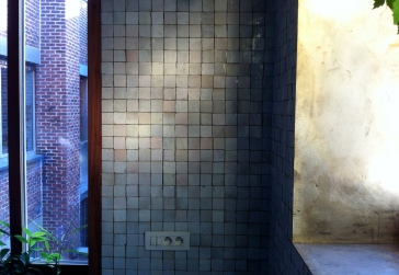 Detail of ceramic tiles and brass finish of kitchen window